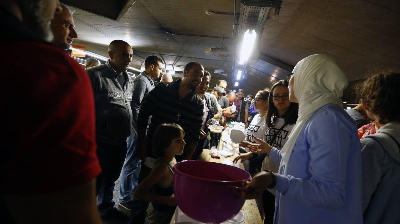 Migrantes y refugiados reciben la comida que les ofrecen unos voluntarios en Salzburgo, Austria (Reuters).