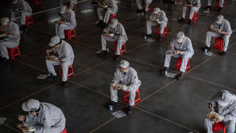 Foto: Trabajadores comen en asientos habilitados y colocados para mantener la distancia prudencial recomendada, en la fábrica Dongfeng Honda, en Wuhan. (EFE)