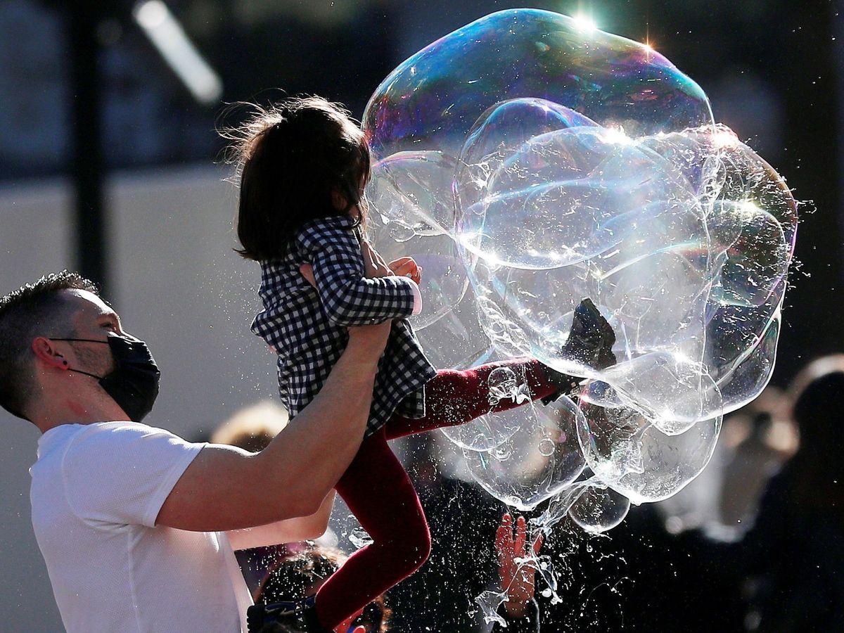 Foto: Un padre juega con su hija a romper pompas de jabón. (EFE)