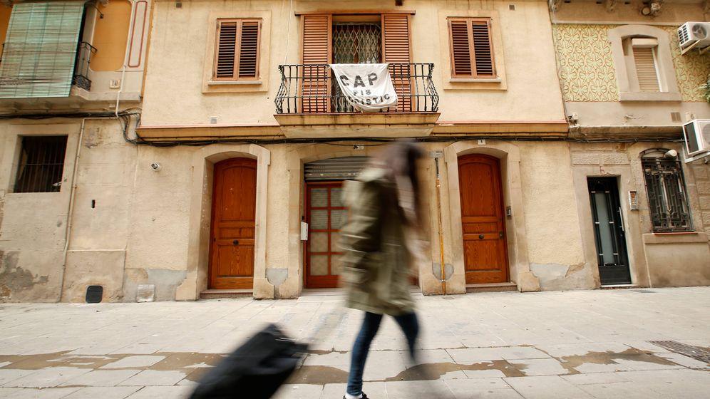 Foto: Una turista arrastra una maleta en la Barceloneta, delante de un cartel que protesta contra la presencia masiva de pisos alquilados. (Reuters/Albert Gea)