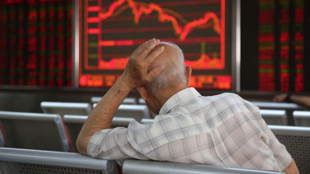 Foto: Un inversor frente a pantallas de información bursátil. (EFE)