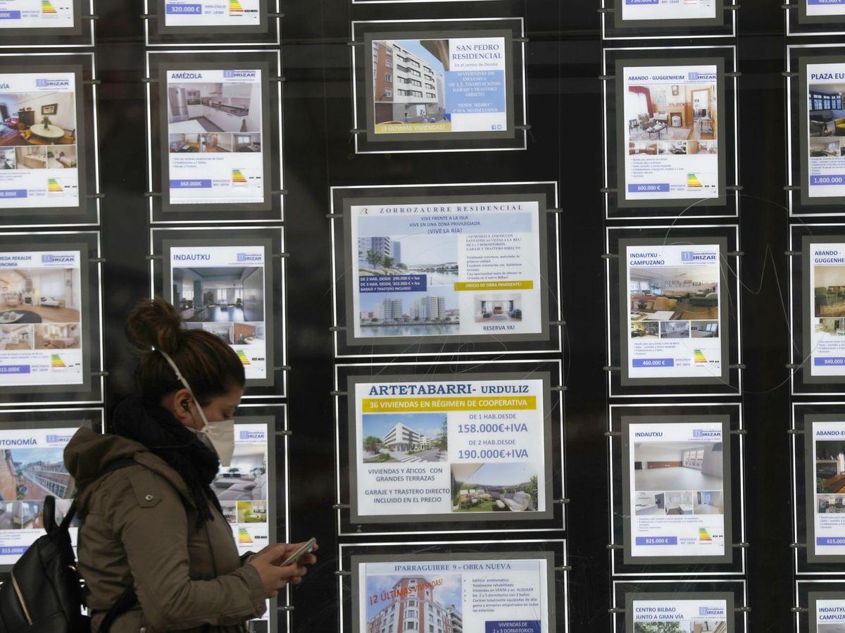 Foto: Una mujer pasa por delante de un portal inmobiliario. (EFE)