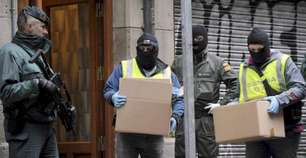 Foto: Agentes de la Guardia Civil sacan material de un inmueble tras la detención de varios etarras. (EFE)