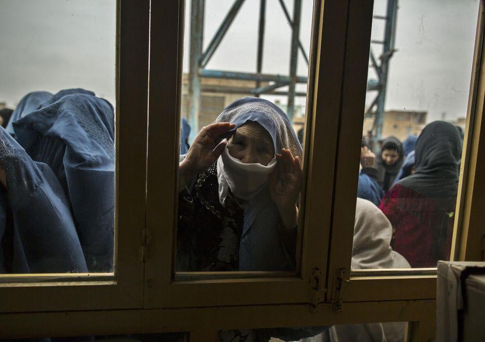 Foto: Una mujer afgana mira el interior de un centro electoral mientras espera para votar en Mazar-i-Sharif (Reuters).