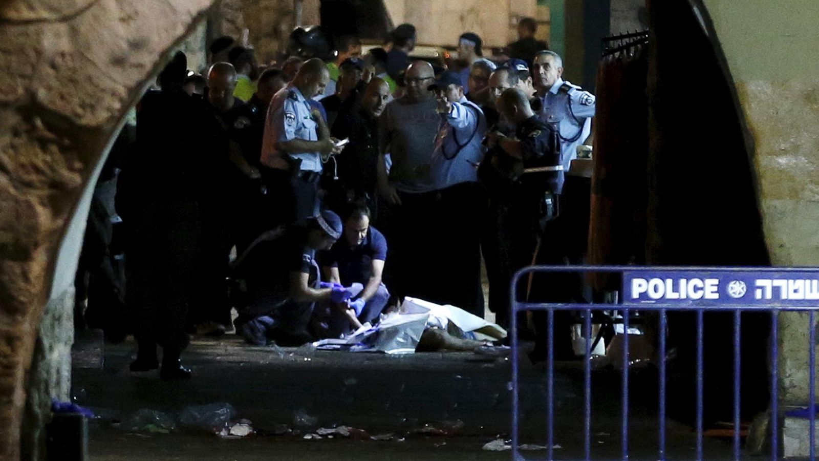 Foto: Personal de seguridad israelí junto al cadáver de un palestino abatido tras acuchillar a dos israelíes en la Ciudad Vieja de Jerusalén, el 3 de octubre de 2015 (Reuters).