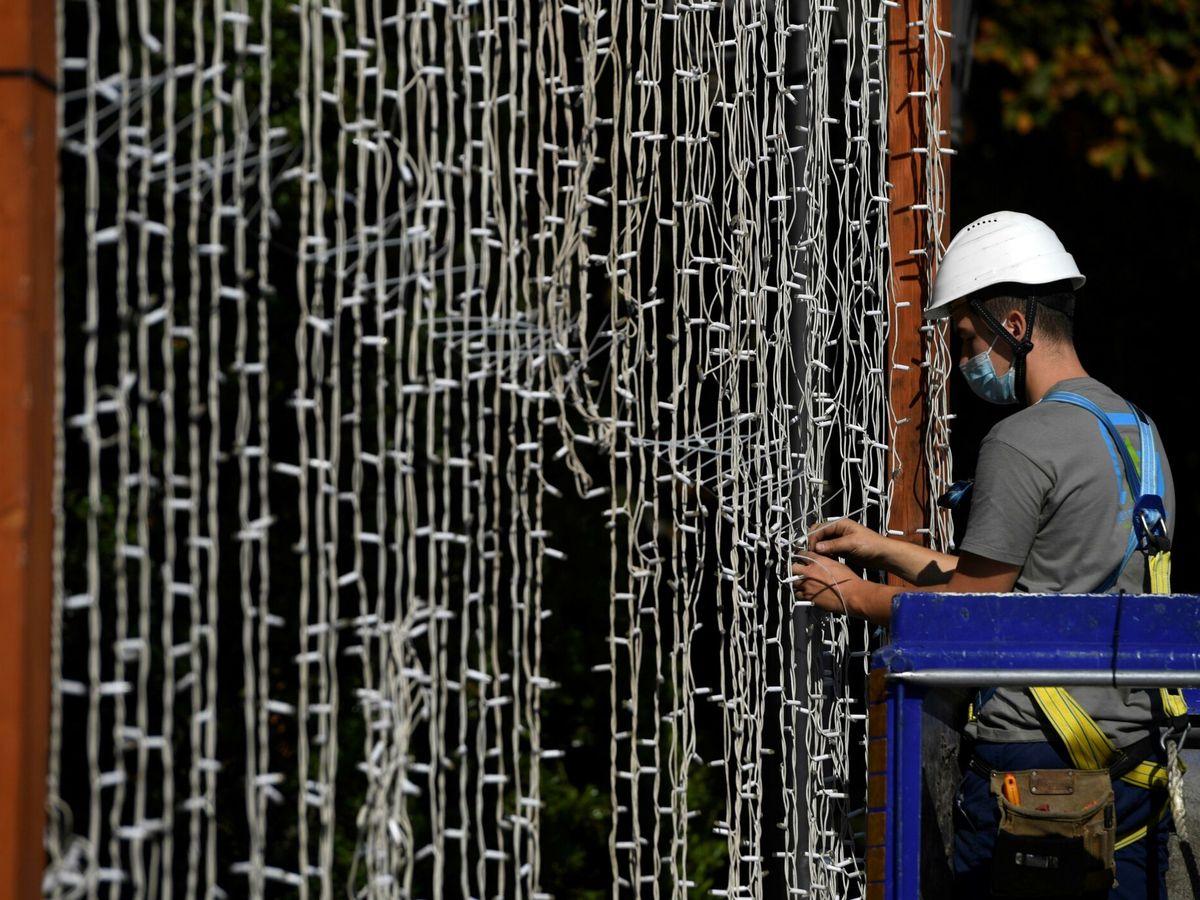 Foto: Un operario coloca una cortina de luces led. (EFE)