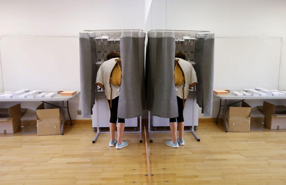 Foto: Un votante, con su imagen reflejada en un espejo, elige su papeleta en un colegio electoral de Pozuelo, en Madrid, en las generales del 26-J de 2016. (EFE)