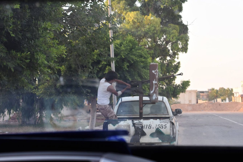 Foto: Un miliciano repara la 'dushka' instalada en una 'pick-up' antes de disparar, en Sirte (Foto: Laura Jiménez).
