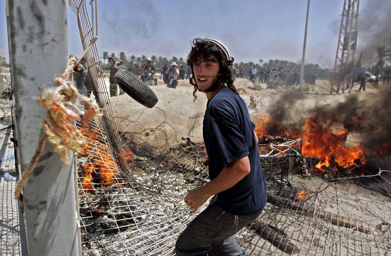Foto: Un colono crea una barricada durante la evacuación del asentamiento ilegal de Shirat Hayam, en la Franja de Gaza, el 18 de agosto de 2005. (Reuters)