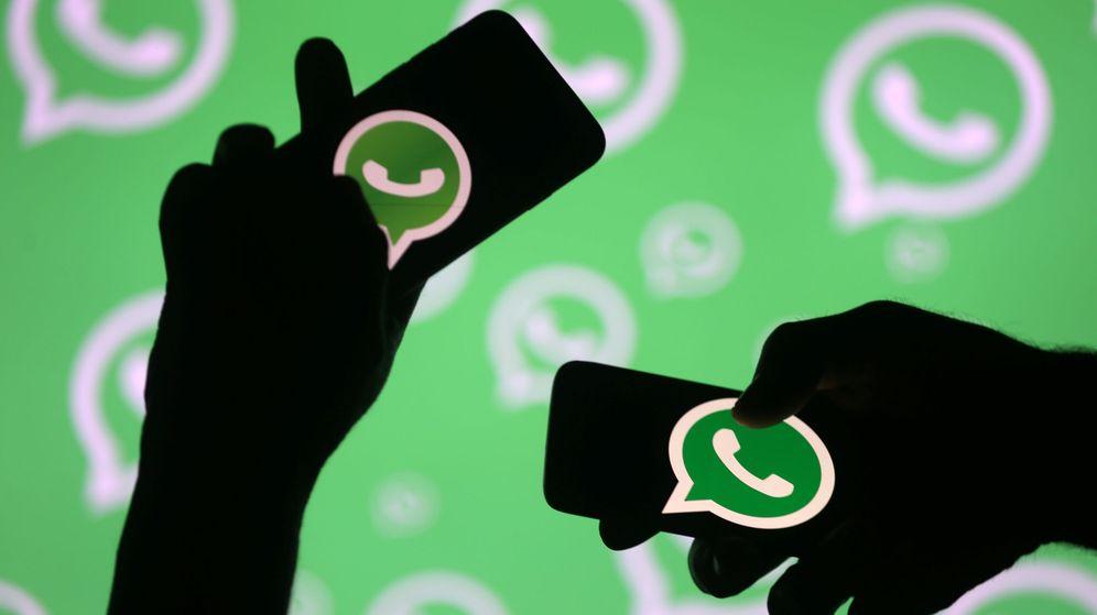 Foto: Dos personas posan portando móviles con el logo de WhatsApp. (Reuters)