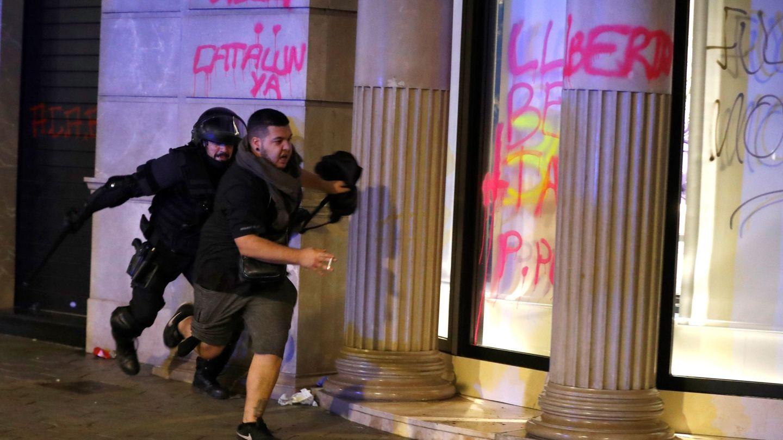 Un miembro de los Mossos d'Esquadra corre tras un manifestante. (EFE)