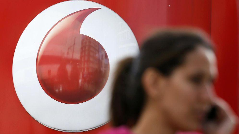 Foto: Una mujer habla por teléfono frente a un logo de Vodafone. (Reuters)