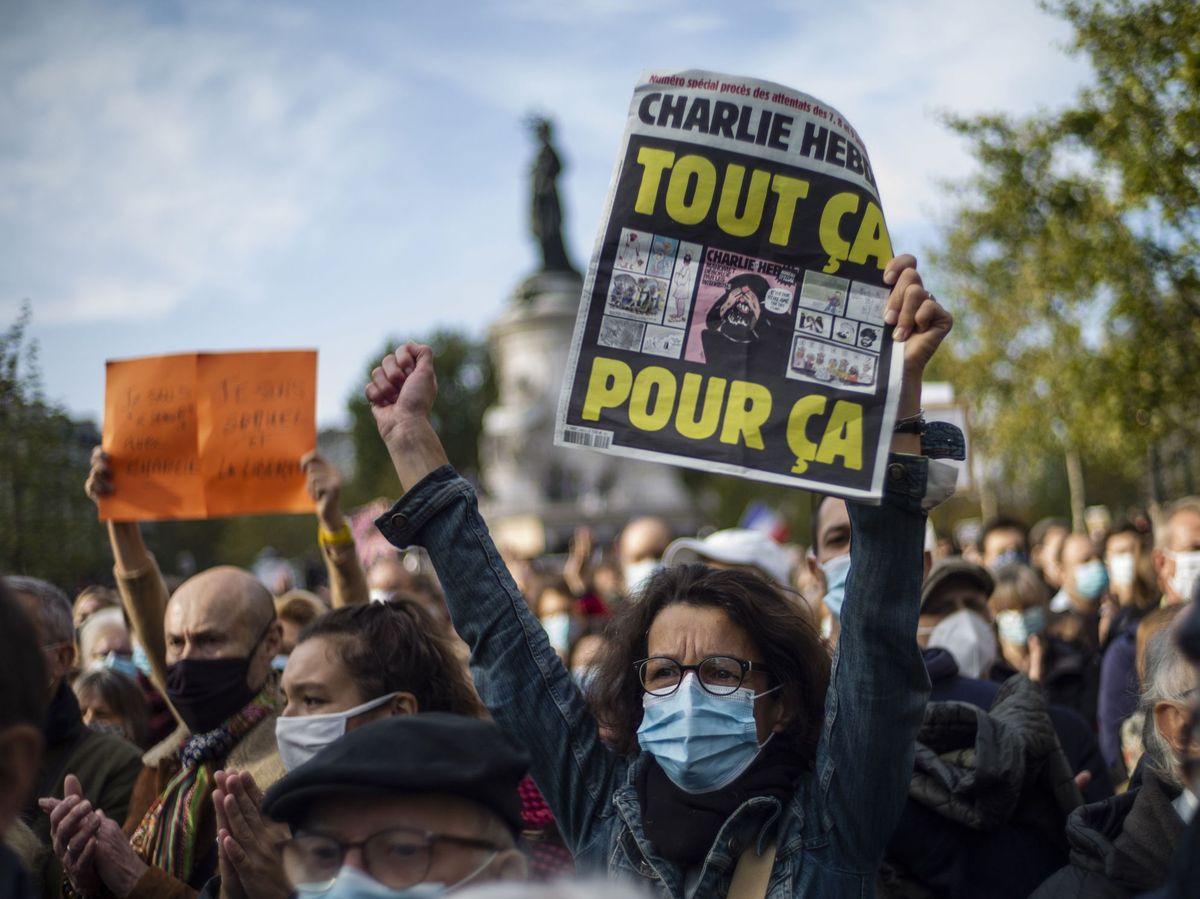 Foto: Una mujer sostiene la polémica portada del semanario satírico 'Charlie Hebdo' en una manifestación. (EFE)