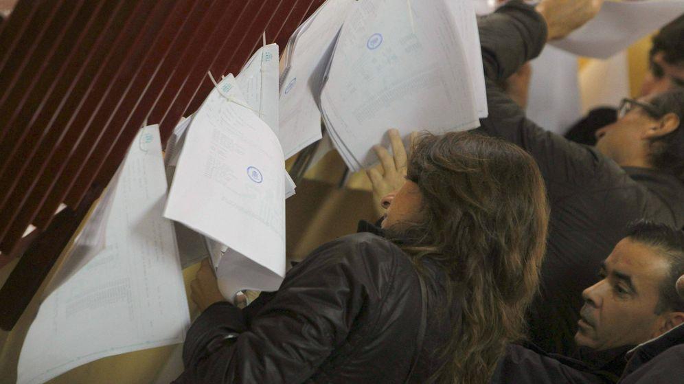 Foto: Varios ciudadanos consultan en las listas de un colegio electoral de Madrid la mesa en la que deben votar. (EFE)