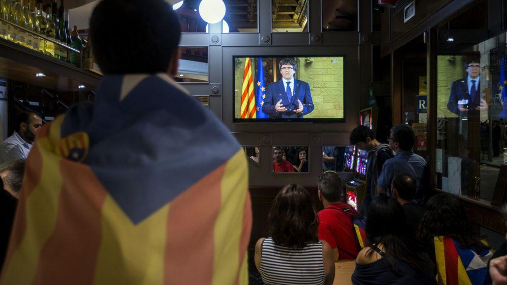 Foto: Un grupo de ciudadanos sigue desde una pantalla de televisión la declaración institucional del presidente de la Generalitat, Carles Puigdemont. (EFE)