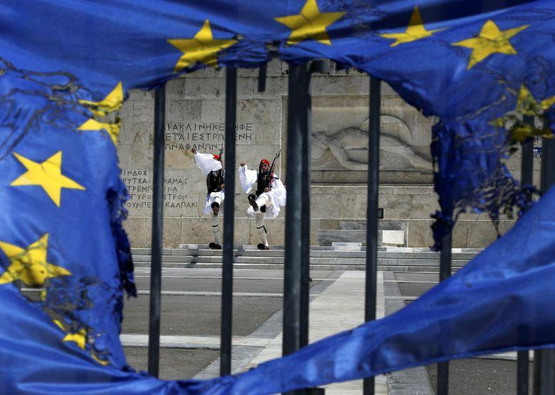 Guardias presidenciales griega fotografiados a través de una bandera de la UE rota en Atenas (Reuters).