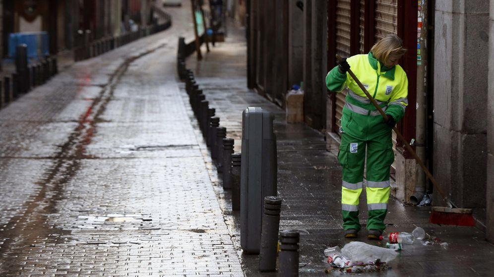 Foto: Una trabajadora de los Servicios de Limpieza de Madrid recoge las basuras y desperdicios que quedan en las inmediaciones de la Puerta del Sol de Madrid (Efe)