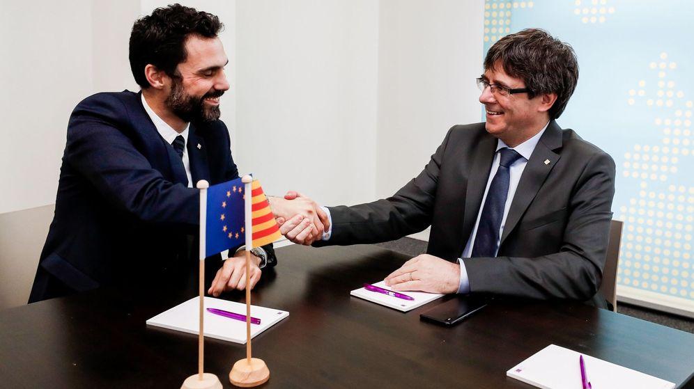 Foto: El expresidente de la Generalitat Carles Puigdemont estrecha la mano del presidente del Parlament, Roger Torrent. (Efe)
