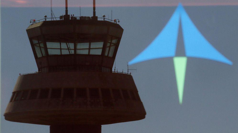 Foto: Una torre de control se refleja en una puerta de cristal con un logo de Aena en el aeropuerto de Barcelona. (Reuters)