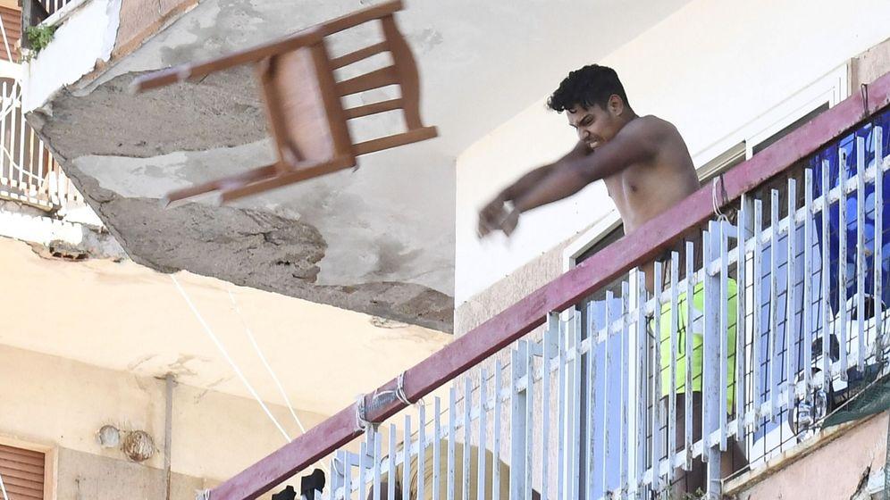 Foto: un hombre tira una silla por la ventana en Mondragone, aislado por un brote. (EFE)