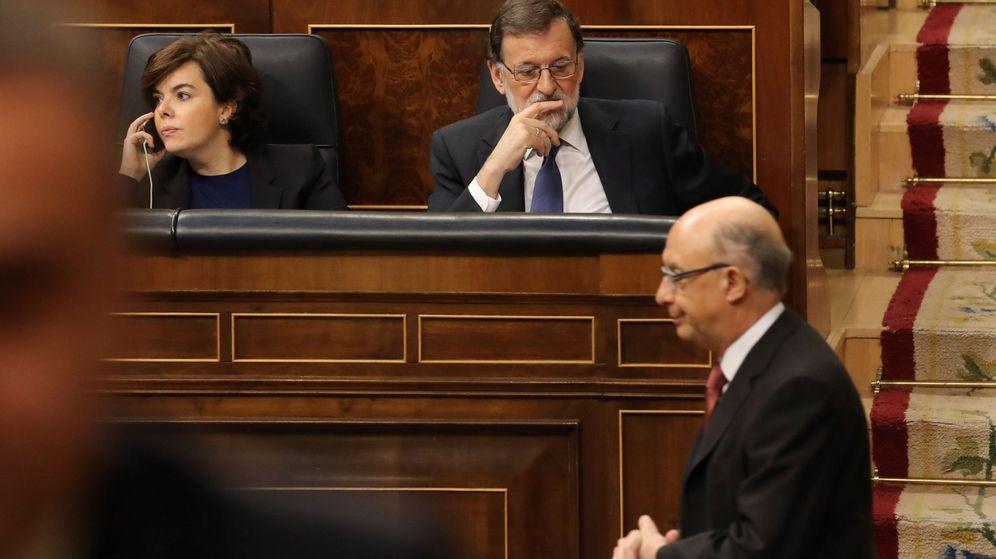 Foto: El ministro de Hacienda y Función Pública, Cristóbal Montoro, pasa junto al presidente del Gobierno, Mariano Rajoy (detrás-d), y la vicepresidenta Soraya Sáenz de Santamaría. (EFE)