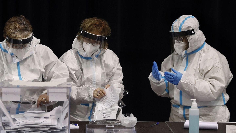 Miembros de las mesas de votación se colocan los trajes de protección EPI en el colegio electoral de las Cotxeres de Sants. (EFE)