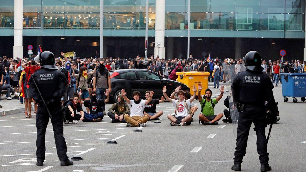 Foto: Miembros de los Mossos d'Esquadra controlan a las centenares de personas que se agolpan ante el Aeropuerto del Prat. (EFE)