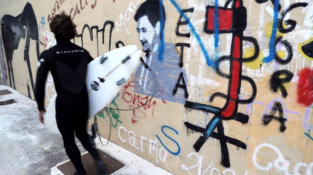 Foto: Un surfista pasa junto a una pintada a favor de la banda terrorista ETA en San Sebastian. (EFE)