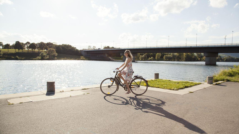 Foto: Una mujer monta en bici por Viena, junto al Danubio. (Manuela Larissegger/Corbis)