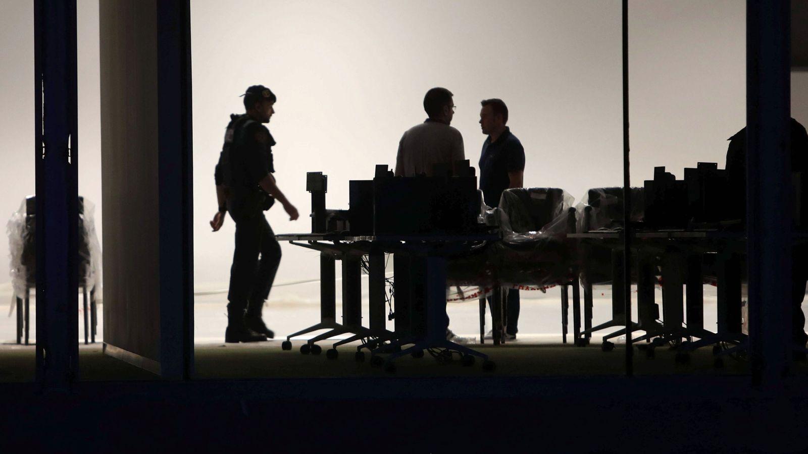 Foto:  Agentes de la Guardia Civil requisando información relativa al 1-O. (EFE)