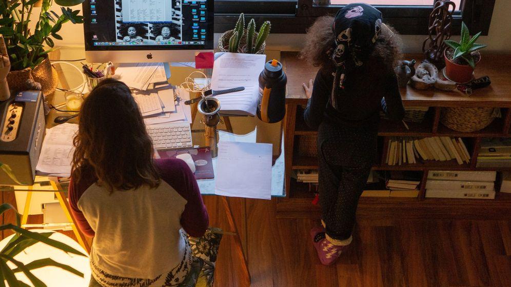Foto: Una mujer teletrabaja en su casa mientras su hija juega a su lado. (EFE)
