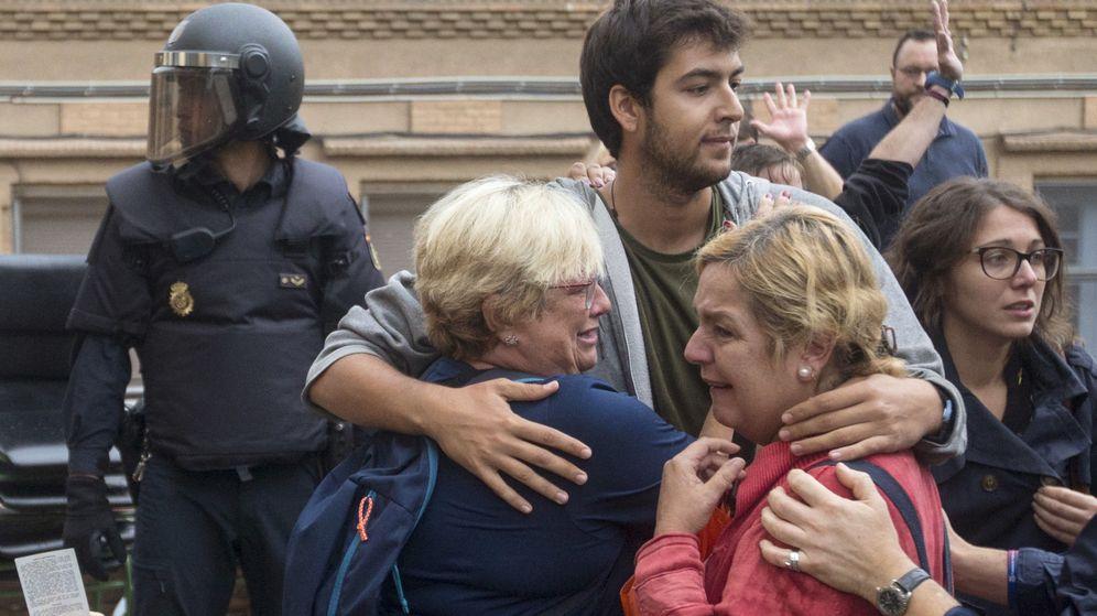Foto: Varias personas lloran en el exterior del Instituto Can Vilumara de L'Hospitalet de Llobregat el 1-O. (EFE)