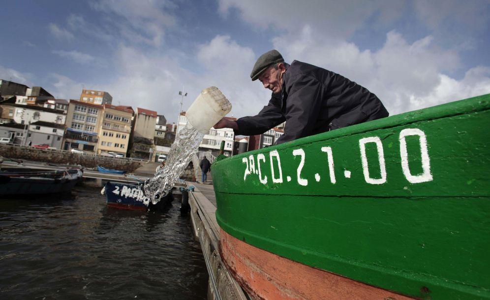 Foto: Un hombre achica agua de su barca en el puerto de Fisterra, La Coruña. (EFE)