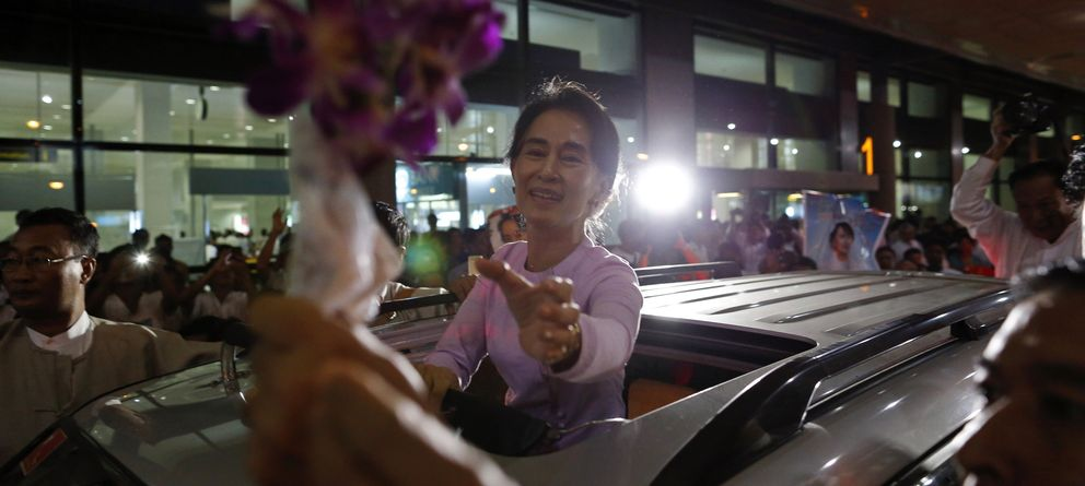Foto: La líder opositora Aung San Suu Kyi recibe unas flores de un simpatizante en el aeropuerto de Rangún, en Myanmar. (Reuters)