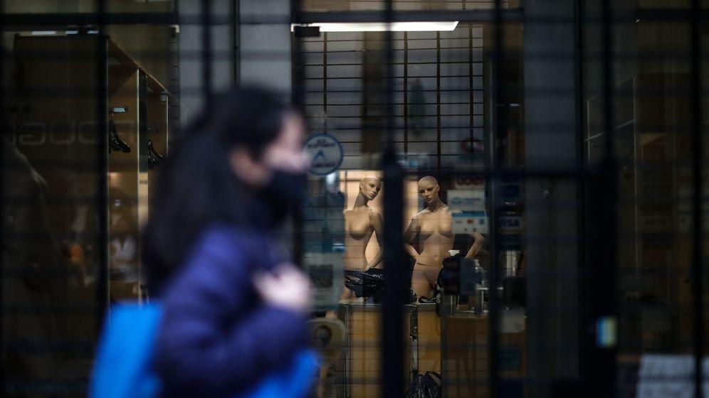 Foto: Una mujer pasa ante un local cerrado. (EFE)