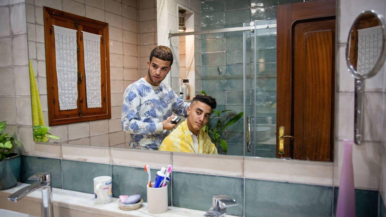 Kamal corta el pelo a varios jóvenes, también habla perfectamente el español. (F. Ruso)