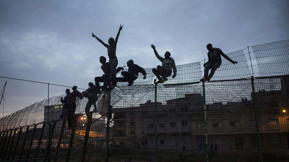 Foto: Un grupo de inmigrantes subsaharianos que piden amparo encaramados en la alambrada fronteriza de Melilla. (EFE)