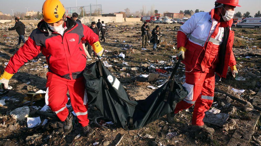 Foto: Miembros de la Media Luna Roja colectan restos tras el accidente de avión cerca de Teherán. (EFE)