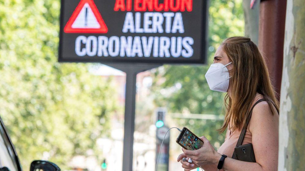Foto: Una mujer espera el autobús junto a un panel informativo en Sevilla. (EFE)