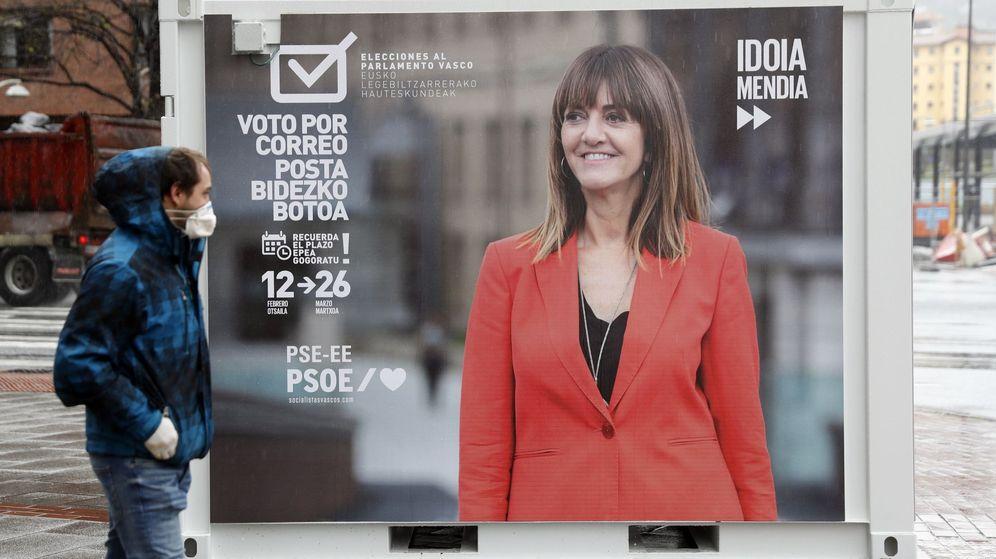 Foto: Un ciudadano con mascarilla, pasa por delante de un cartel preelectoral en Bilbao. (Efe)