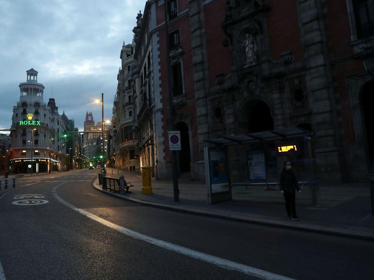 Foto: Una mujer espera al autobús en la calle Alcalá durante la epidemia. (Susana Vera / Reuters)