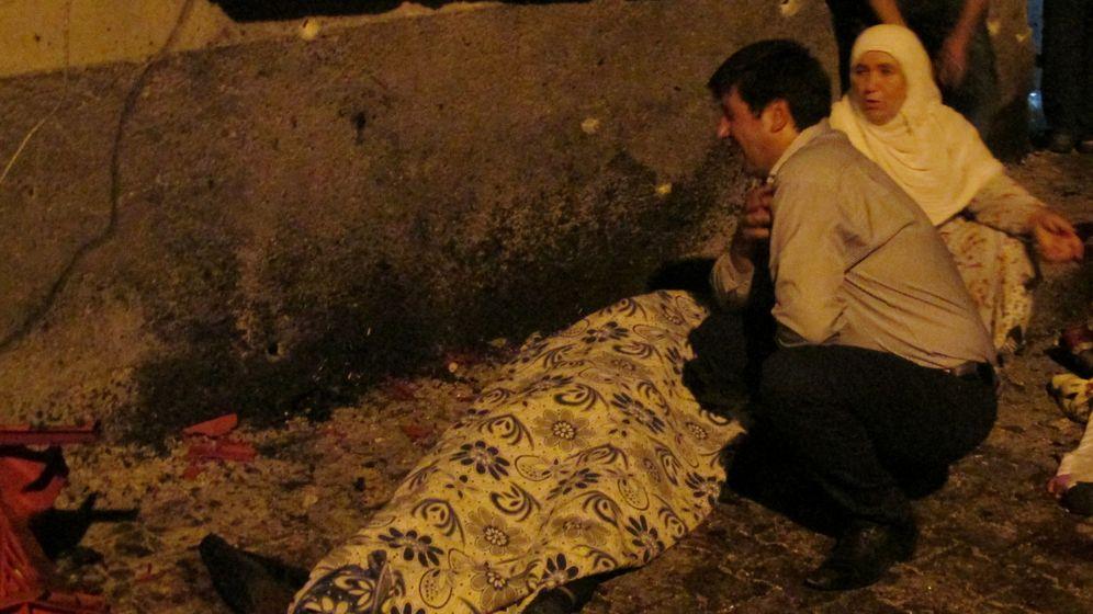 Foto: Un hombre y una mujer junto a un cuerpo de una víctima. (Reuters)