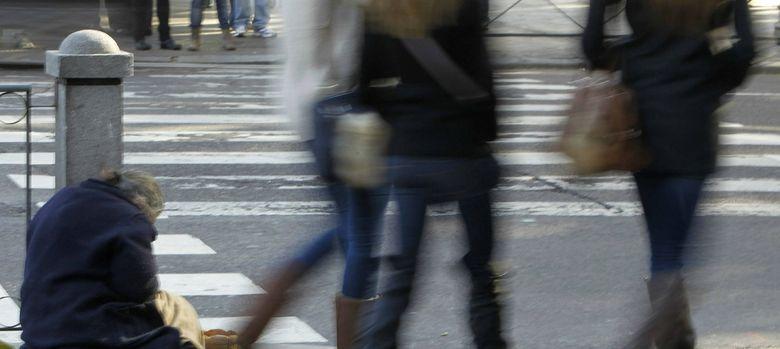 Foto: Un mendigo pide limosna ante la indiferencia de los transeúntes (Efe)