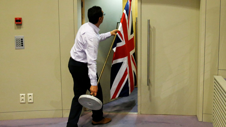 Un trabajador de la Comisión Europea retira una bandera británica. (Reuters)