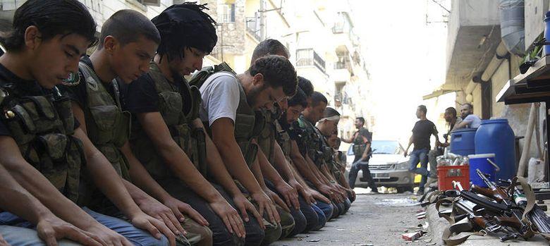 Foto: Combatientes del Ejército de Liberación Sirio rezan en una calle de Alepo (reuters).
