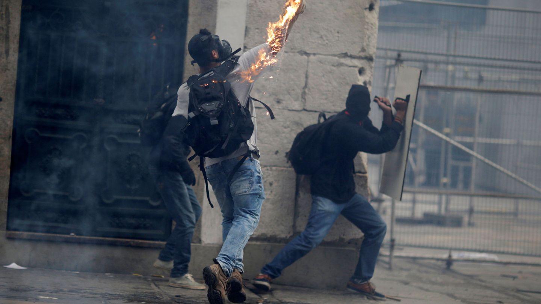 Un manifestante arroja un cóctel molotov contra la policía durante los disturbios en la huelga general. (Reuters)