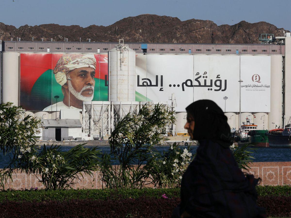 Foto: Una mujer pasa frente a un retrato del sultán Qaboos en Muscat, Oman. (Reuters)