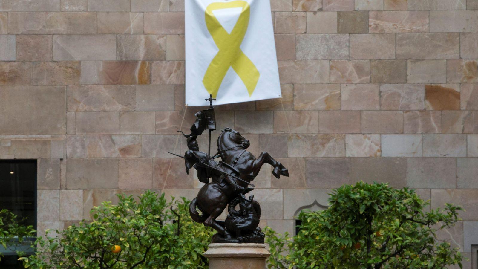 Foto: Una pancarta con un lazo amarillo cuelga de una de las paredes del Pati dels Tarongers. (EFE)