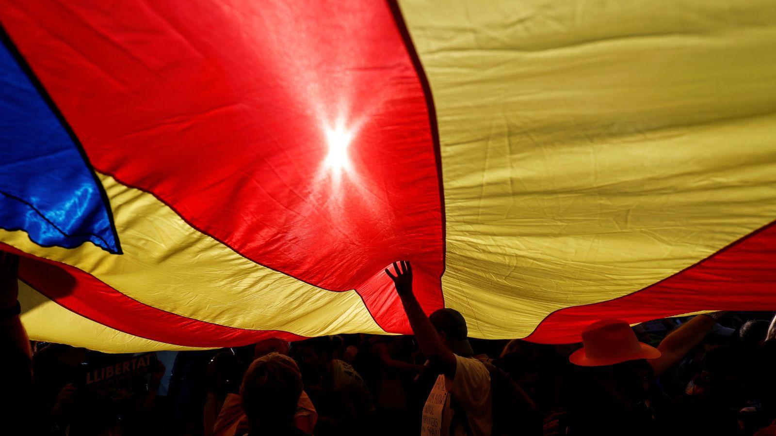 Foto: Un grupo de manifestantes bajo una bandera 'estelada' gigante en la manifestación contra el encarcelamiento de 'los Jordis'. (Reuters)