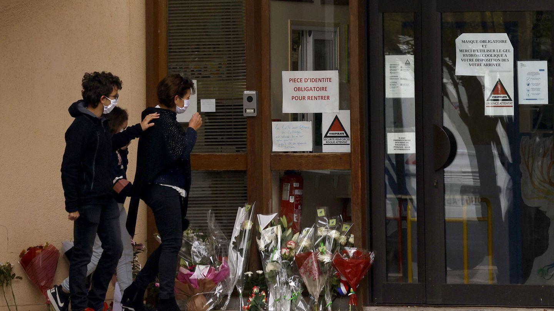 Padres y alumnos dejan flores en la puerta del instituto en el que trabajaba el profesor asesinado. (EFE)